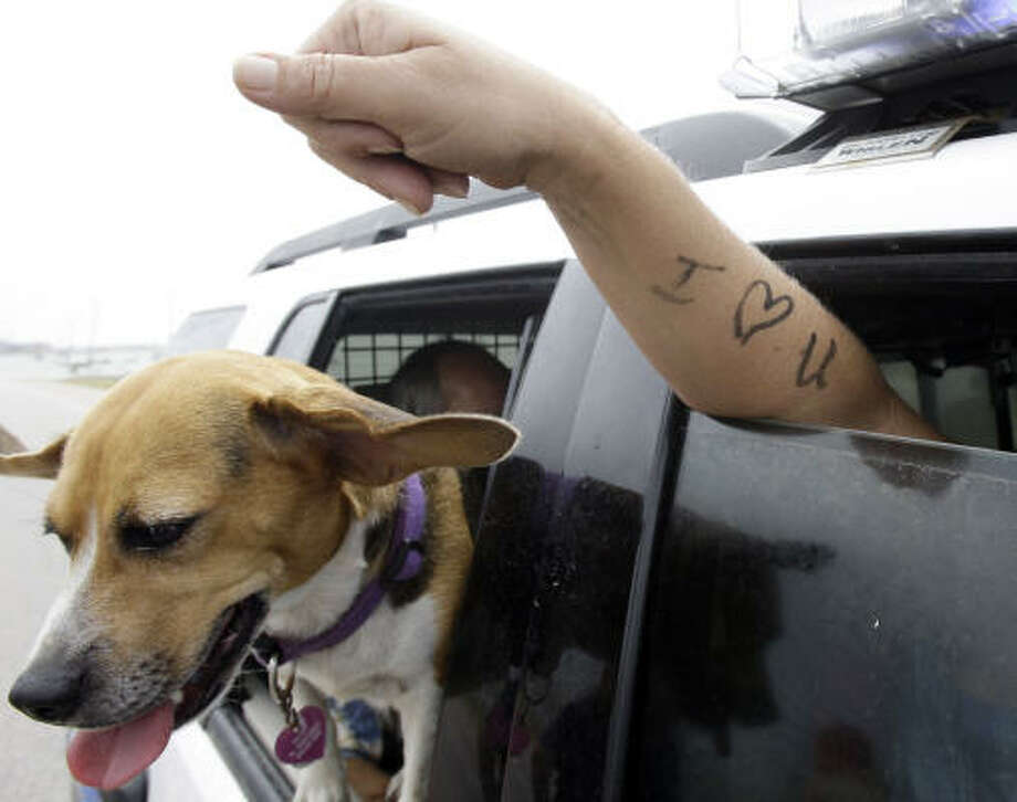 Dondi Fields, with her dog Sandyi Beach,  shows the message to her children she wrote on her arm before she was evacuated by Surfside police and firefighters as Hurricane Ike caused flood waters in their neighborhood, in Surfside Beach on Friday, Sept. 12. Photo: Eric Gay, AP
