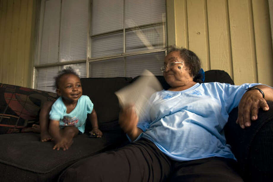 Oakwood Gardens apartment complex resident, Fannie Sanders, 59, uses a book to cool herself while keeping an eye on family friend, India Davis, 1, Tuesday. Like many in Houston, she has been living without power for 11 days. Photo: Johnny Hanson, Houston Chronicle