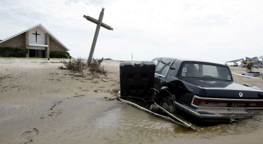 A car is covered by mud and sand in front of a Crystal Beach church. Photo: Eric Gay, AP