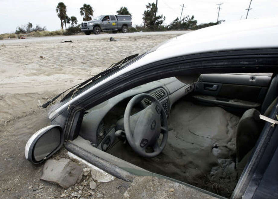 Sand swallows up a car at Crystal Beach. Photo: Eric Gay, AP
