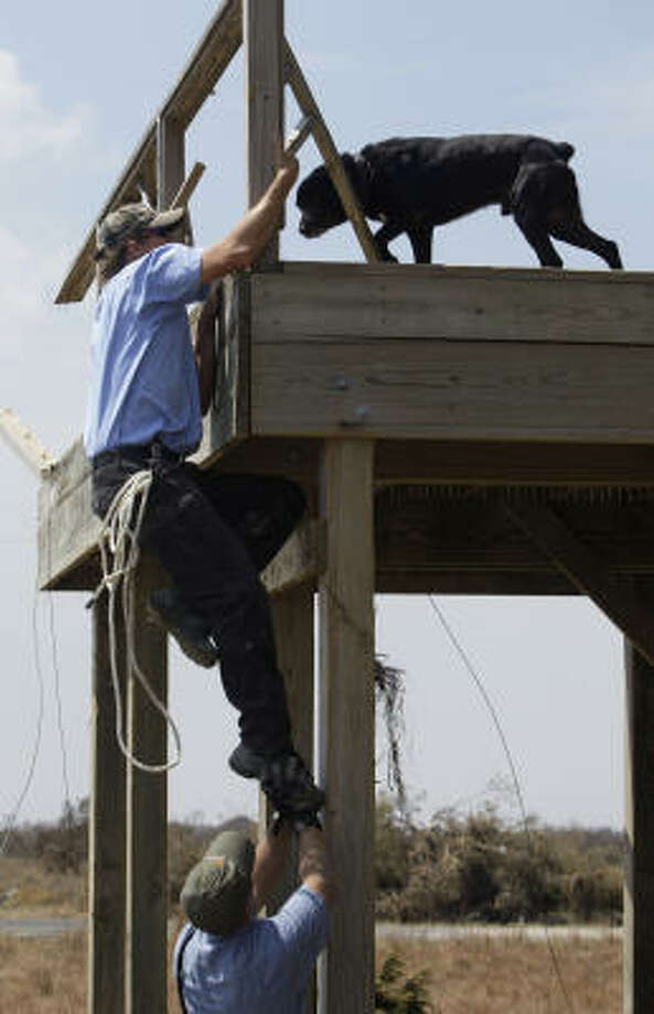 Eugene McAvin is pushed to a porch by Josh Henderson to rescue a dog at Crystal Beach. Photo: Eric Gay, AP