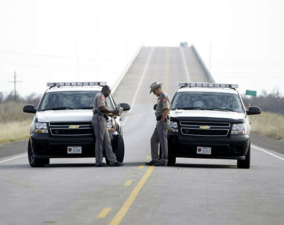 State Troopers J. Jones, left, and R. Venegas guard the entrance to High Island on Highway 124, just before High Island Bridge 1, Sept. 17. Photo: Karen Warren, Chronicle