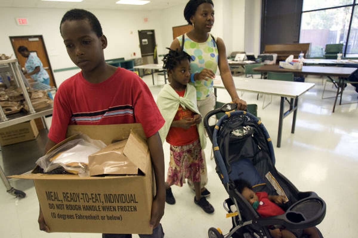 Jose Sanchez, 12, gets a box of MREs for his family including his sister Cynthia, 8, center, mother Sandra Sanchez, right, and brother Isaac, 5 months, at the Hurricane Ike Recovery Assistance Comfort Station at the Third Ward Multi-Service Center. The family is still living without power.