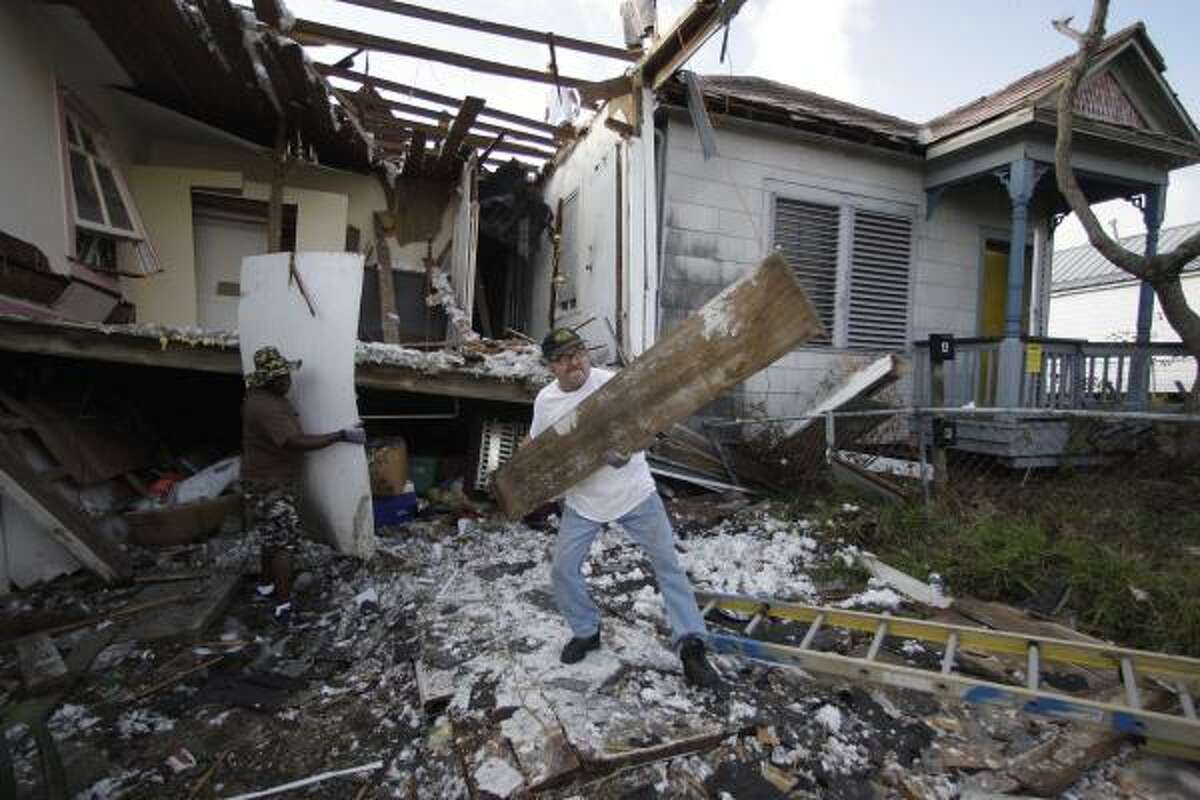 Scot Adams help demolish a Galveston house destroyed by Hurricane Ike. Repairing damages homes was an ongoing effort until recently. The City of Galveston will cease repairing and will begin demolishing and rebuilding.