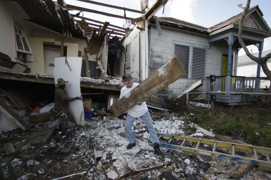 Scot Adams help demolish a Galveston house destroyed by Hurricane Ike. Repairing damages homes was an ongoing effort until recently. The City of Galveston will cease repairing and will begin demolishing and rebuilding. Photo: Rick Bowmer, AP