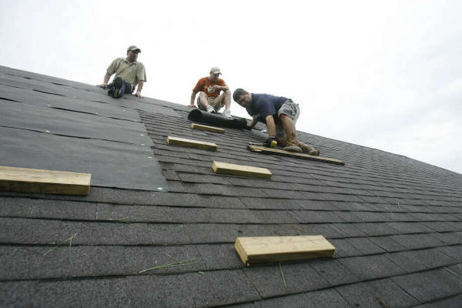 The men fix damage on the roof from Ike. Photo: Nick De La Torre, CHRONICLE