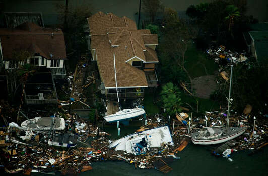 Boats and debris are seen surrounding waterfront houses on Galveston Island. Photo: Smiley N. Pool, Chronicle