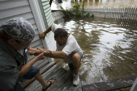 Terry Panchot, left, helps Charles Cormier reach the flooded front porch of their home in Galveston on Aug. 13. Photo: Brett Coomer, Chronicle