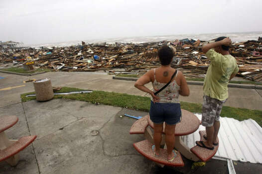 """I can't believe this. It's unreal,"" said Galveston resident Henry Vasquez, shown with his wife, Mary, at what's left of Murdock's Pier and Hooters along Seawall Boulevard in Galveston Sept. 13. Photo: Johnny Hanson, Chronicle"