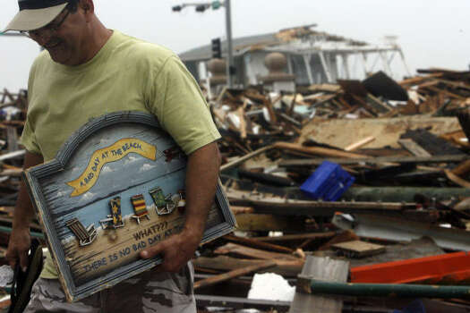 Vasquez grabs a sign from the rubble of Murdock's Pier and Hooters on Sept. 13. Photo: Johnny Hanson, Chronicle