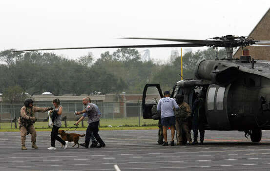 Rescue victims move from a National Guard helicopter to waiting buses at Stingaree Stadium in Texas City. Photo: Kevin M. Cox, AP
