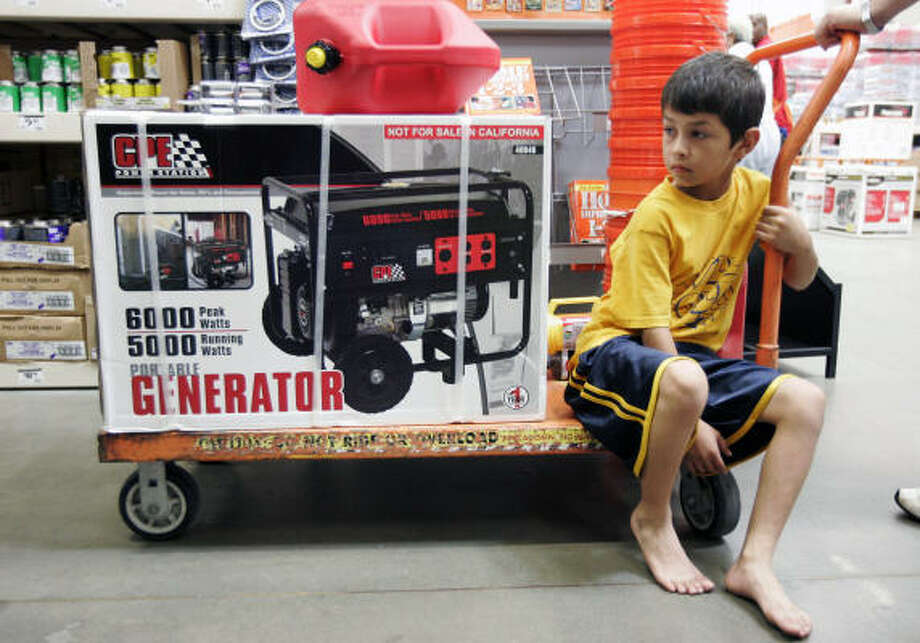 Javier Guerra, 8, of Channelview sits in flatbed cart next to a generator his family is purchasing at a Home Depot store in Corpus Christi. Guerra and his family, from Houston, were buying supplies before heading back home. Photo: Michael Zamora, AP