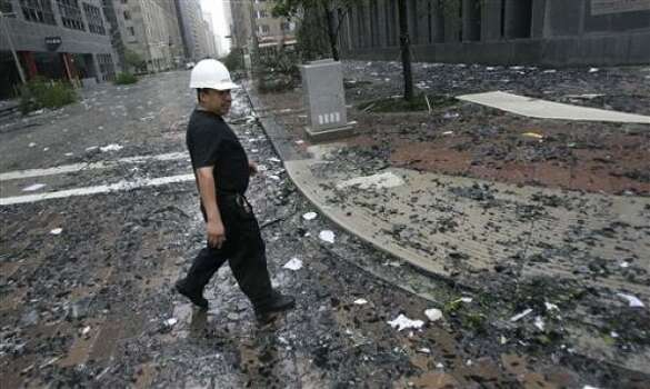 A building maintenance worker walks over shattered glass after winds from Hurricane Ike damaged windows on the JPMorgan Chase Tower. Photo: David J. Phillip, AP