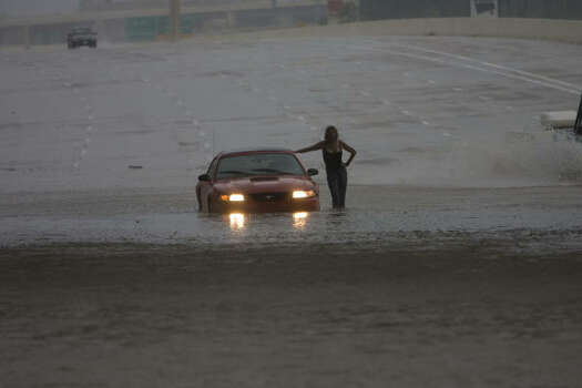 A woman stands near her car in flood waters today on I-10 East near Washington Avenue in Houston. Photo: James Nielsen, Chronicle