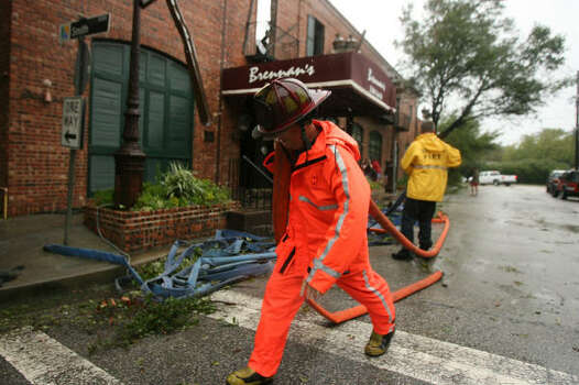 A Houston fireman rolls up fire hoses from an over night blaze at Brennan's when Hurricane Ike hit Houston early Saturday morning. Photo: Billy Smith II, CHRONICLE