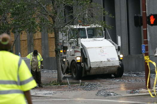 City of Houston Public Works employees clean up the glass pieces along Travis after the JP Morgan Chase Tower was heavily damaged by Hurricane Ike on Sept. 13. Photo: Mayra Beltran, Chronicle