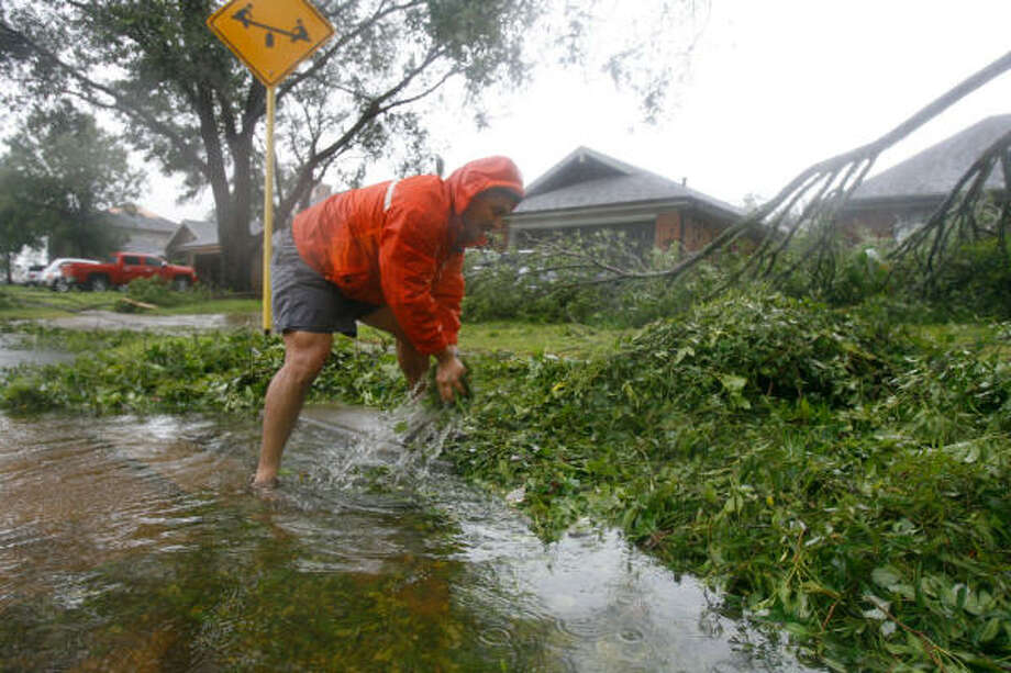 Honorio Velasquez tries to clear a gutter this morning in Pearland. Photo: Nick De La Torre, CHRONICLE