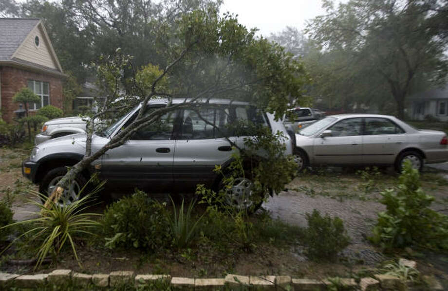 A broken tree limb rest atop an car in the 6600 block of Rolla near Spring Branch. Photo: James Nielsen, Chronicle