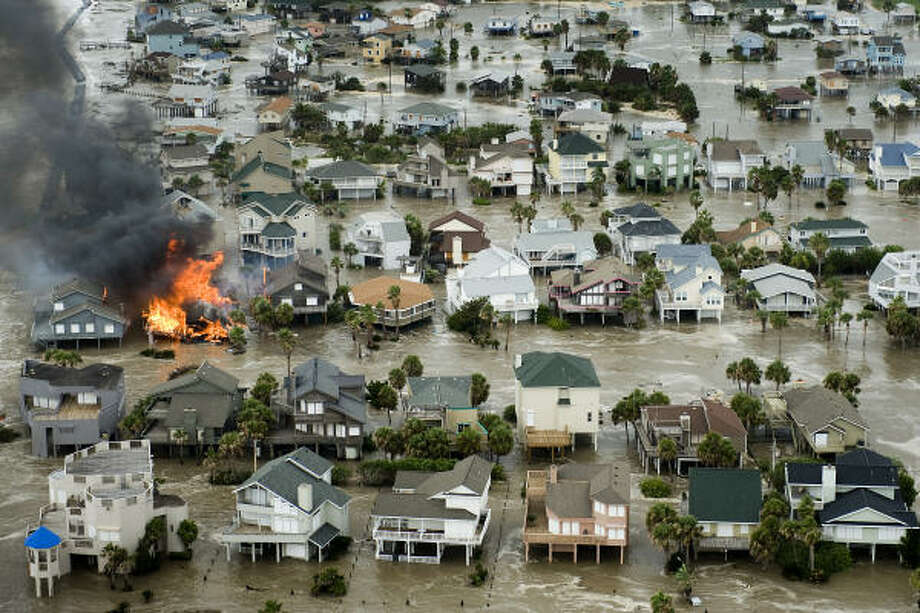 A house is totally engulfed in flames as floodwaters Inundate beach homes on Galveston Island as Hurricane Ike approaches the Texas Gulf Coast, Friday, Sept. 12, 2008. Photo: Smiley N. Pool, Houston Chronicle