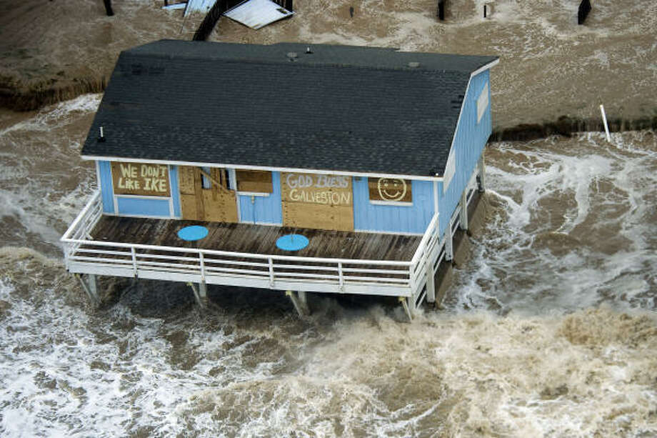 "Surf surrounds a beach house with the messagess ""We Don't Like Ike,"" and ""God Bless Galveston"" pained on plywood covering the windows of the house on Galveston Island as Hurricane Ike approaches the Texas Gulf Coast, Friday, Sept. 12, 2008. Photo: Smiley N. Pool, Houston Chronicle"