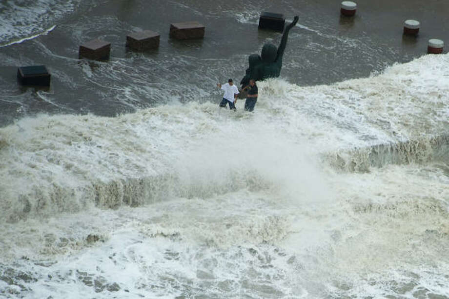 Waves crash over the seawall as two men walk near a memorial to victims of the 1900 storm on Galveston Island, Friday, Sept. 12, 2008. Photo: Smiley N. Pool, Houston Chronicle