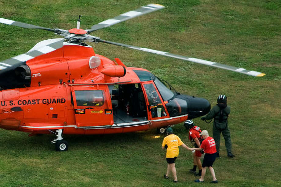 Hurricane Ike evacuees are helped to a U.S. Coast Guard helicopter as they flee flooded Bolivar Peninsula. Photo: Smiley N. Pool, Houston Chronicle