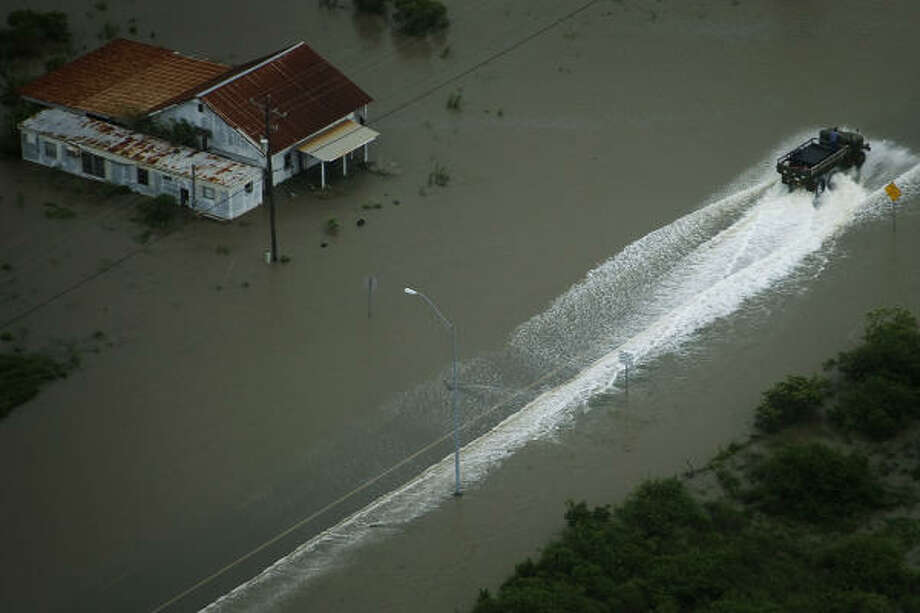 A truck drives through flood waters on the Bolivar Peninsula, Friday, Sept. 12, 2008. Photo: Smiley N. Pool, Houston Chronicle