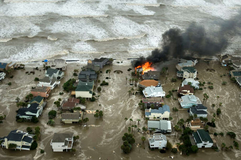 A house is totally engulfed in flames as floodwaters and crashing waves inundated beach homes on Galveston Island, Friday, Sept. 12, 2008. Photo: Smiley N. Pool, Chronicle