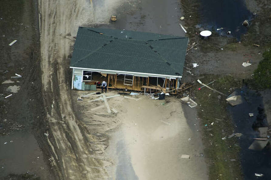 A search worker rests in a house which lies across Highway 87 near Crystal Beach, Monday, Sept. 15,