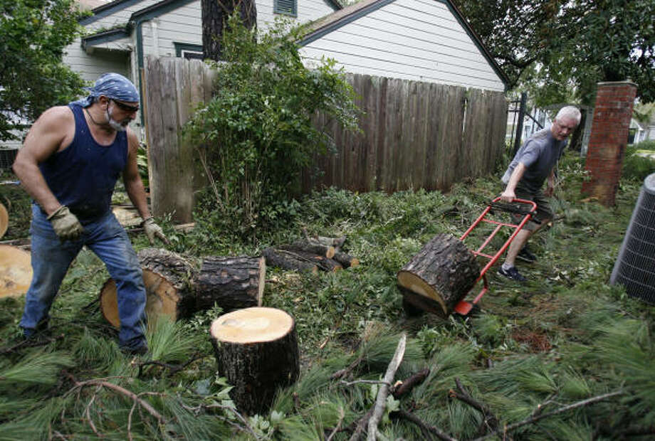 Alex Martinez, left, helps his neighbor, Jerry Kennedy chop down a piece of tree trunk Sept. 14 in Garden Oaks after the tree fell on Kennedy's house during the storm. Photo: Karen Warren, Chronicle