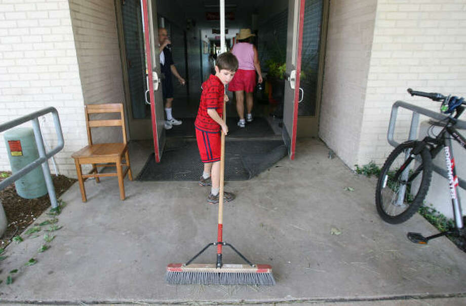 First-grader Cameron Sutton, 7, sweeps a side entrance at Kolter Elementary School Sept. 19 in Houston. Photo: Mayra Beltran, Chronicle