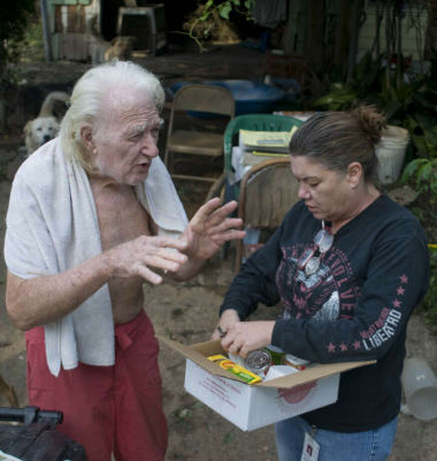 Meals on Wheels volunteer Vicki Waters delivers food and water Sept. 16 to 77-year-old Bill Morgan at his southeast Houston area home. Photo: Steve Ueckert, Chronicle