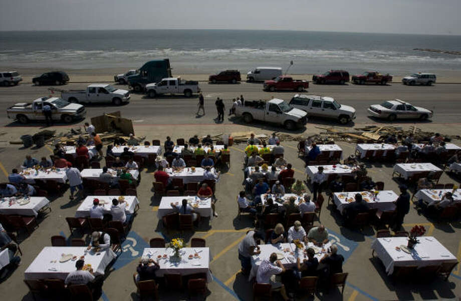 White linen table cloths greeted first responders and utility crews along Seawall Boulevard as Gaido's restaurant served up a shrimp broil lunch Sept. 18 to those who are helping and cleaning up Galveston Island. Photo: Johnny Hanson, Chronicle