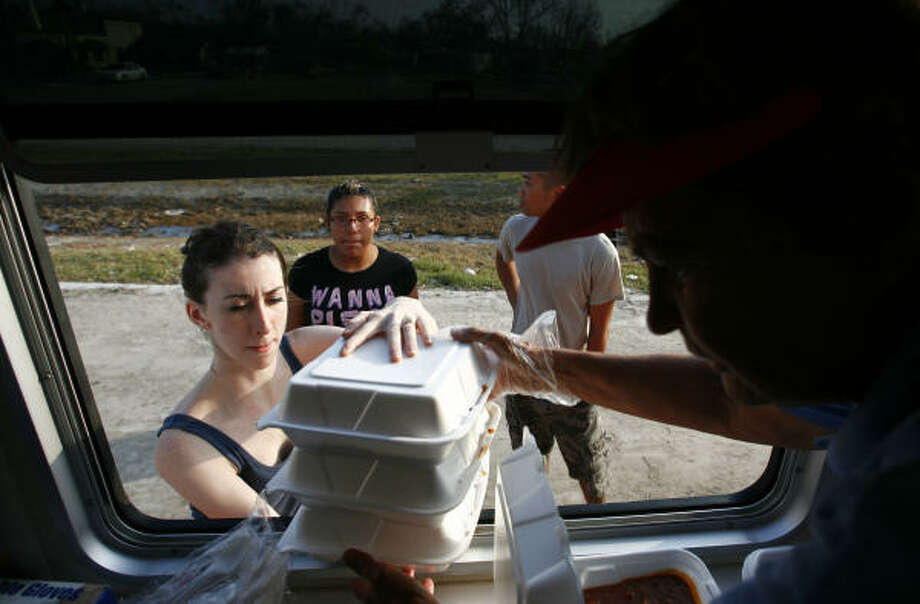 Kathryn Schlemmer, left, is handed a stack of dinners by American Red Cross worker Eunice Swenson Sept. 19 in San Leon, while Julis Leyva, 15, center and Alex Cao, both of San Leon, wait. Photo: Sharon Steinmann, Chronicle