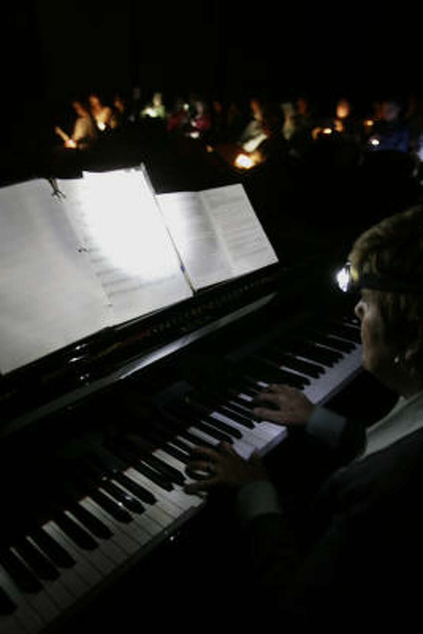 Ann Frohbieter plays for Congregation Emanu El as it performs Selichot, a service held to ask God for forgiveness before the Jewish High Holidays. Flashlights were used during the service because of a power outage due to Hurricane Ike.