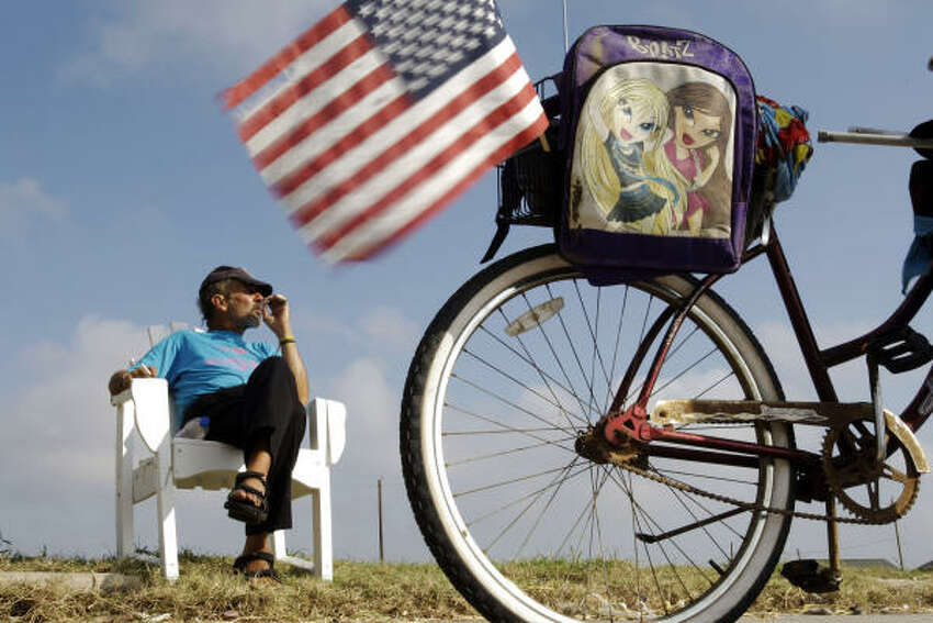 Randall Dowdell listens to church service on the radio on the back of his bike in Galveston.