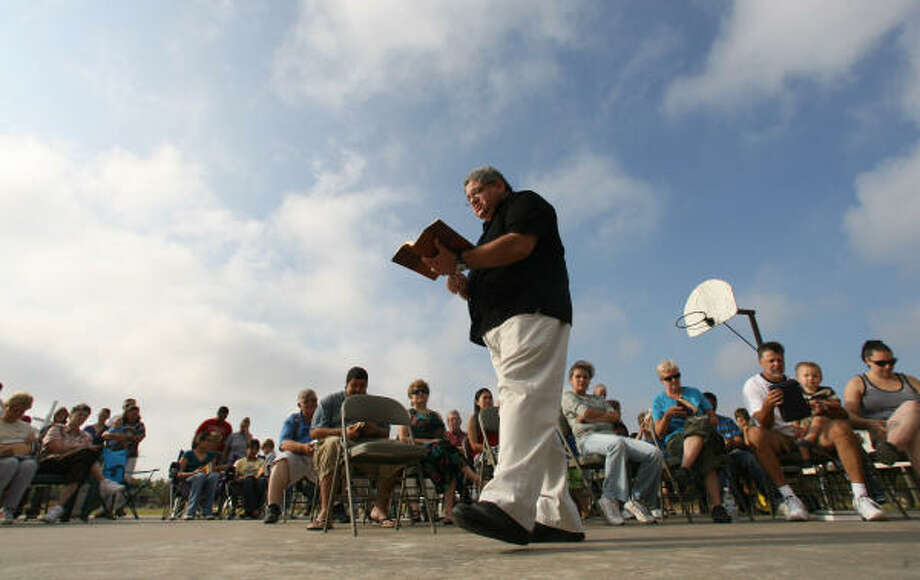 Pastor of Oak Island Baptist church Eddie Shauberger preaches on the church's basket ball court during worship service in The Oak Island neighborhood near Anahuac, Texas. The church suffered extensive damage caused by surge from Hurricane Ike forcing the congregation to meet outdoors for their weekly service, Sunday, Sept. 21, in Oak Island. Photo: Billy Smith II, Chronicle