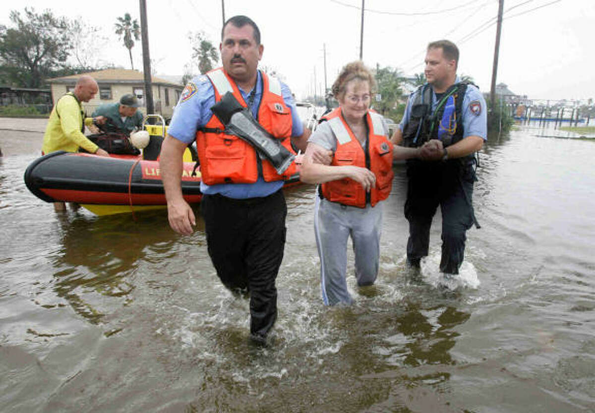 Dolores Gabriles, 71, is helped from a rescue boat by police captain Walter Braun, left, and officer Jeremy Smart in Galveston.