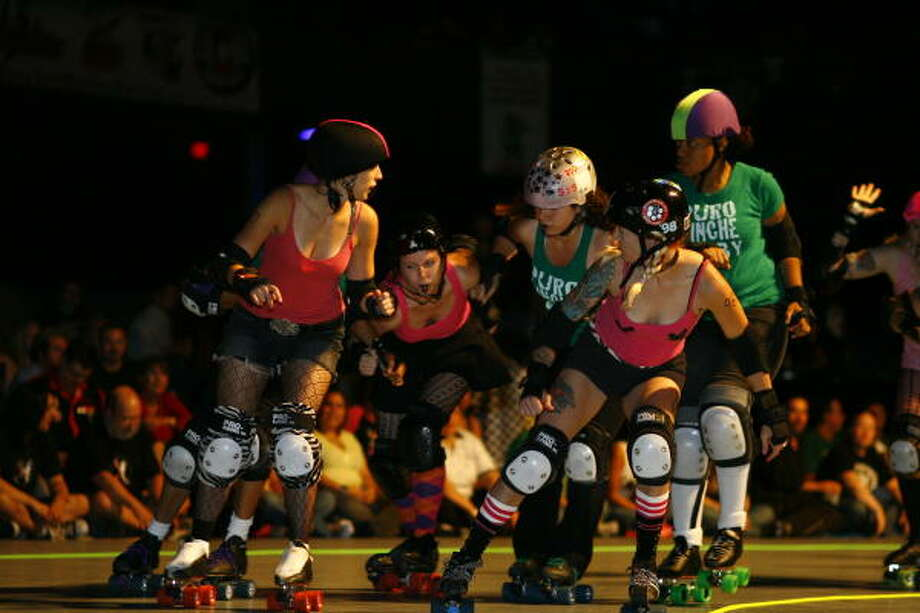 Blockers from Assassination City Derby, of Dallas, try to keep the Las Tejanas Derby, of San Antonio, from stopping their jammer from getting through and scoring during the 'Governors Cup' of roller derby at the Verizon Wireless Theater Sunday in Houston. Photo: Nick De La Torre, Chronicle