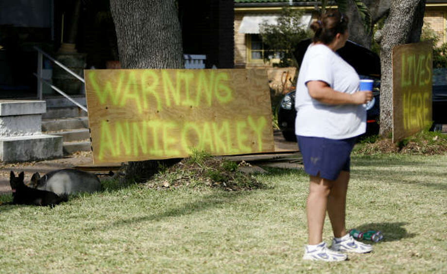 "Teresa Castillo stands in front of her Galveston home on Saturday with a sign that reads ""Warning Annie Oakley Lives Here."" Photo: Karen Warren, Chronicle"