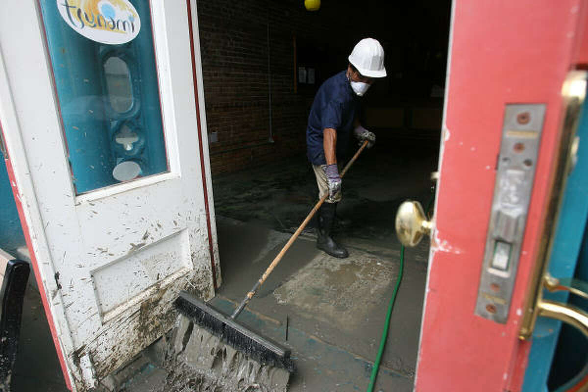 A worker sweeps out mud from inside the Tsunami Restaurant in an effort to reopen the business after Hurricane Ike flooded the first floor in Galveston.