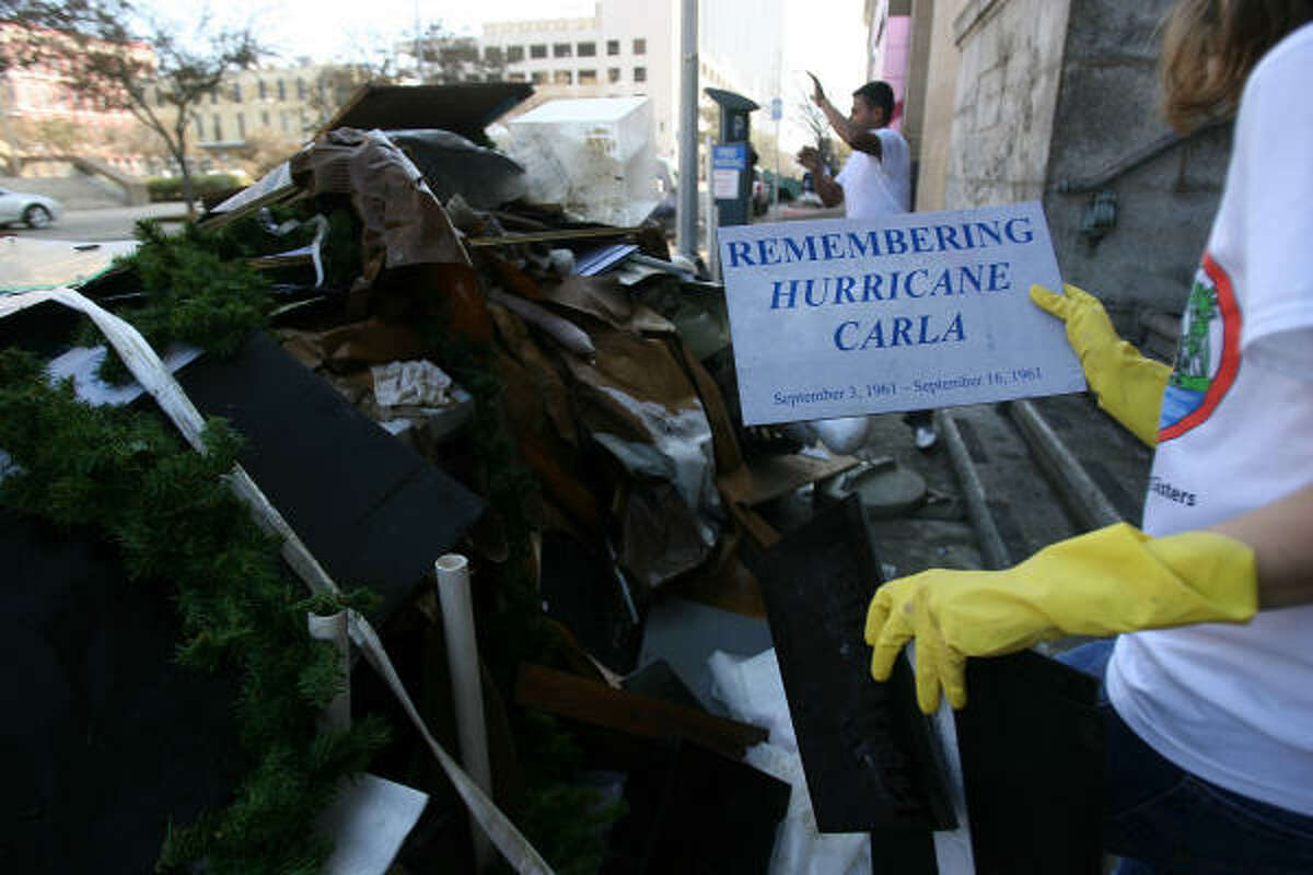 Jennifer L. Marines, assistant director, holds damaged old exhibits as workers throw out debris from the flooded basement at the Galveston County Historical Museum.