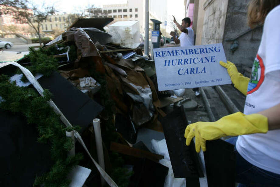 Jennifer L. Marines, assistant director, holds damaged old exhibits as workers throw out debris from the flooded basement at the Galveston County Historical Museum. Photo: Mayra Beltran, Chronicle