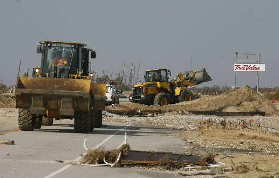 Texas Department of Transportation crews work to clear Highway 87 in Gilchrist on the Bolivar Peninsula Sept. 20 in the aftermath of Hurricane Ike. Photo: Kevin M. Cox, AP