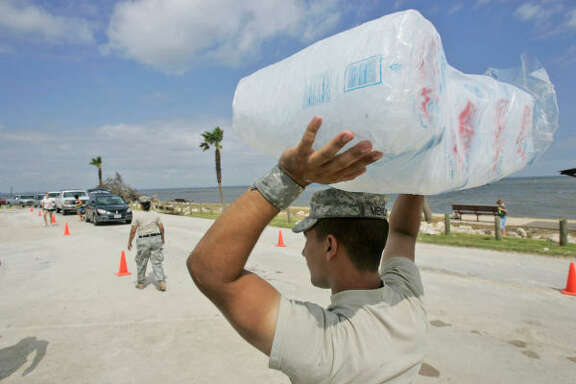 Spc. John Mendoza of the Texas National Guard waits to load up ice for a long line of motorists in the aftermath of  Hurricane Ike in Bacliff.