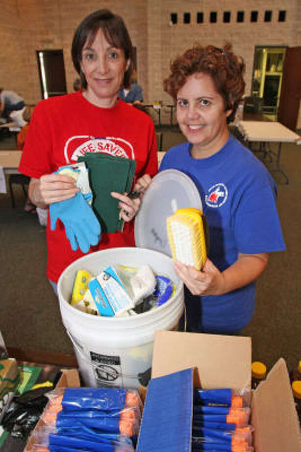 "FLOOD BUCKETS:  Volunteers Lorna Bradley, left,  and Griseida Garcia at St. Peter's United Methodist Church in Katy hold ""flood buckets"" with household cleaners that they organized for 200 families in the East Houston Ridgemont HUD development. Photo: Suzanne Rehak, For The Chronicle"