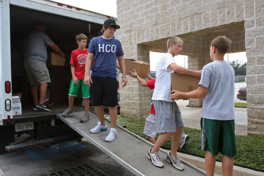 Volunteers at St. Peter's United Methodist Church in Katy load a truck with boxes of donated food to be sent to 200 families in the Ridgemont HUD development in East Houston. Photo: Suzanne Rehak, For The Chronicle