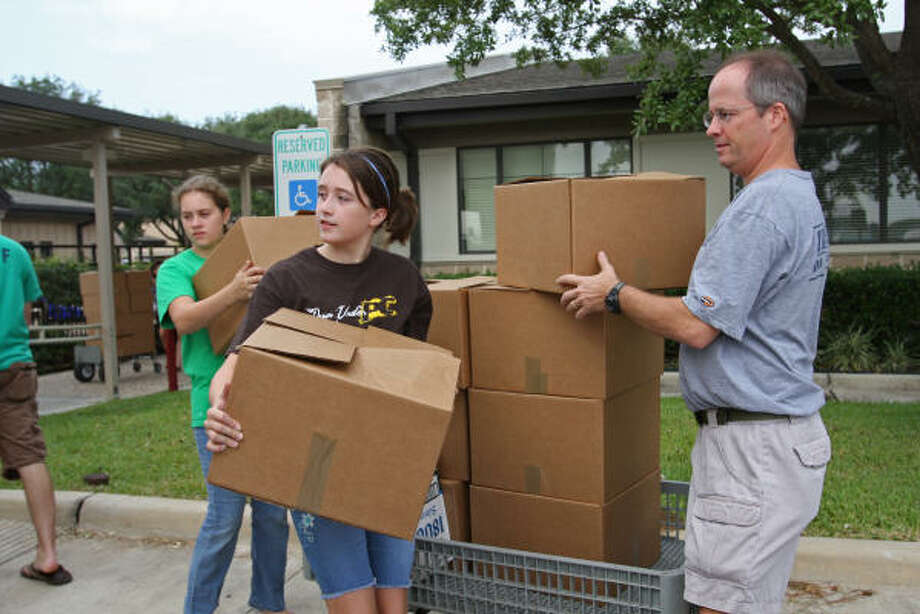 Volunteers, from left, Kelsey Wells, 12; Audrey Tucker, 11; and Dennis Hendon load boxes of food in a truck for delivery to East Houston. Photo: Suzanne Rehak, For The Chronicle