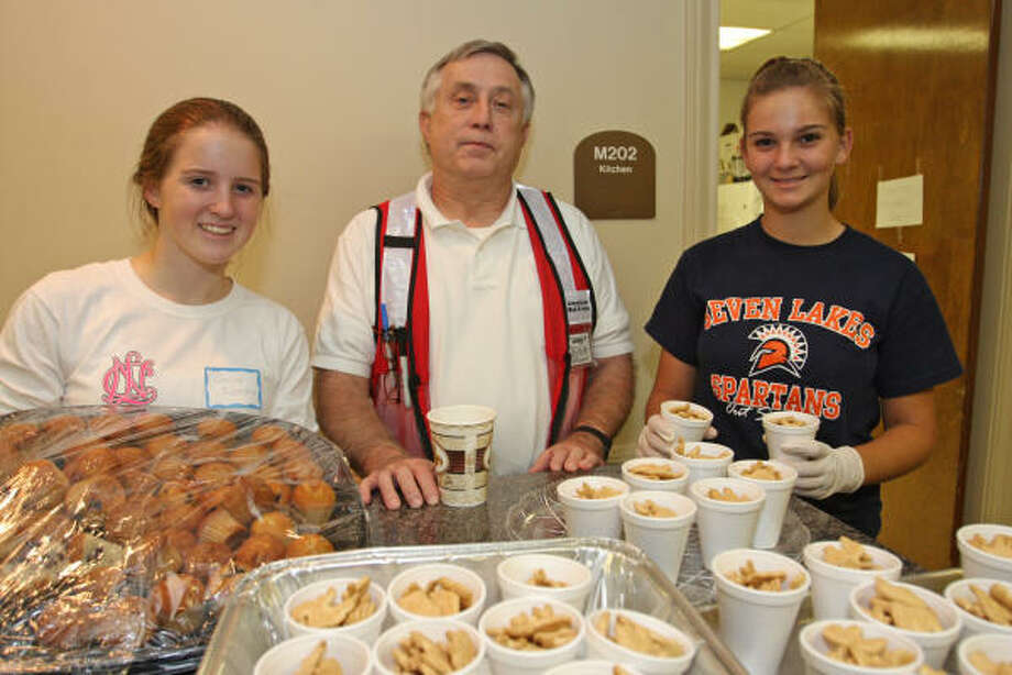 Preparing snacks for volunteers and evacuees, from left, are Caroline Richardson, 14, ninth-grader at Seven Lakes High School; Jim Read, American Red Cross volunteer from Starkville, Miss.; and Drew Hartt, 14, ninth-grader at Seven Lakes. Photo: Suzanne Rehak, For The Chronicle