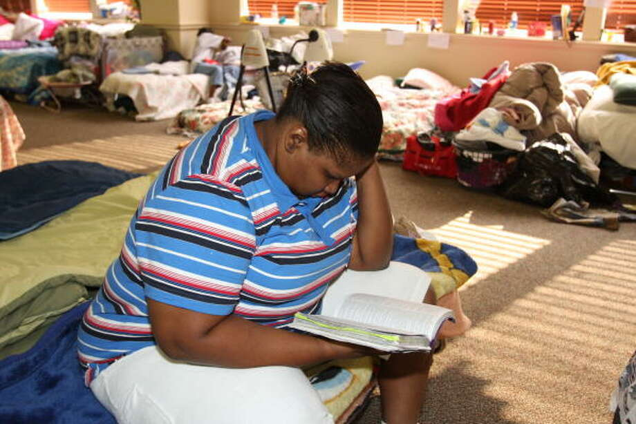 Tameka Nelson, a Hurricane Ike evacuee from Houston, sits on the edge of her mattress and reads the Bible. Photo: Suzanne Rehak, For The Chronicle